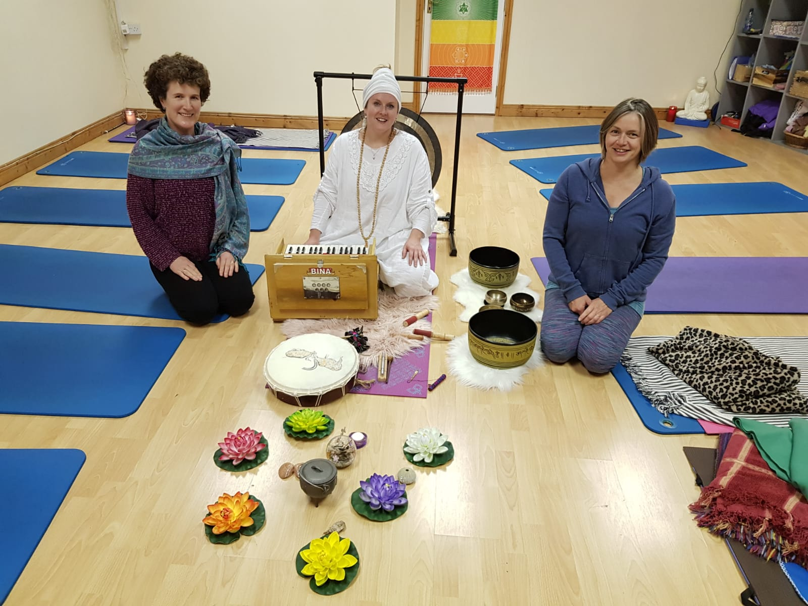 3 people seated on floor of studio with sound gong and lotus flowers