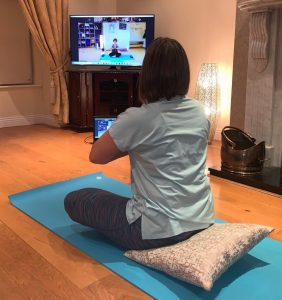 person practising yoga at home in front of computer